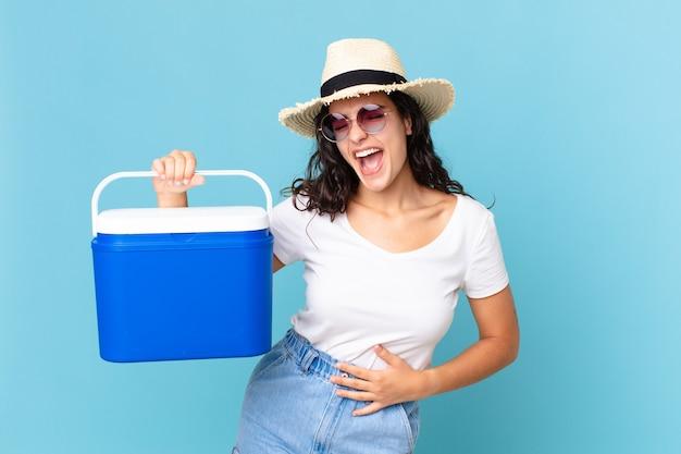 Linda mulher hispânica rindo alto de uma piada hilária segurando uma geladeira portátil
