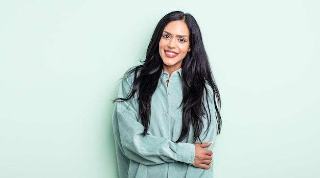 Linda mulher hispânica rindo tímida e alegre, com uma atitude amigável e positiva, mas insegura