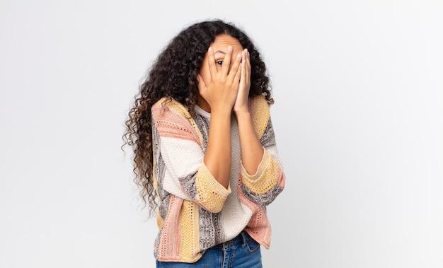 Linda mulher hispânica se sentindo assustada ou envergonhada, espiando ou espionando com os olhos semicobertos pelas mãos