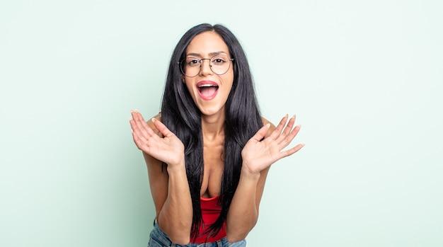 Linda mulher hispânica se sentindo chocada e animada, rindo, maravilhada e feliz por causa de uma surpresa inesperada