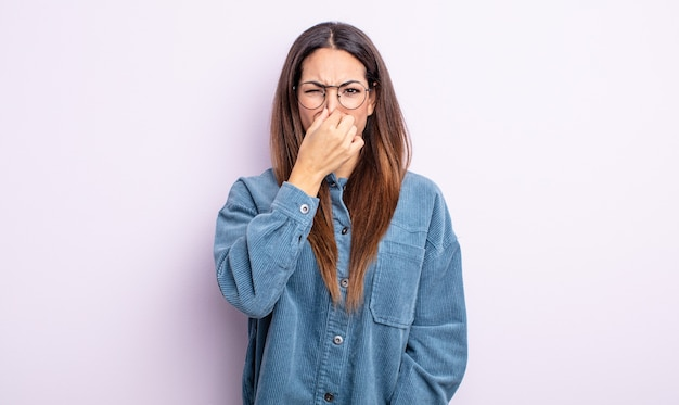 Linda mulher hispânica se sentindo enojada, segurando o nariz para evitar cheirar um fedor desagradável e desagradável