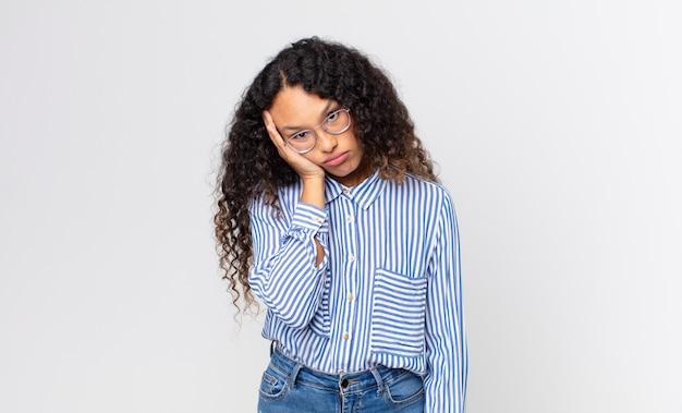 Linda mulher hispânica se sentindo entediada, frustrada e com sono depois de uma tarefa cansativa, enfadonha e tediosa, segurando o rosto com a mão