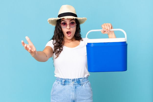 Linda mulher hispânica se sentindo extremamente chocada e surpresa segurando uma geladeira portátil