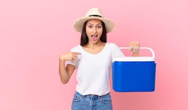 Linda mulher hispânica se sentindo feliz e apontando para si mesma com um animado e segurando uma geladeira portátil