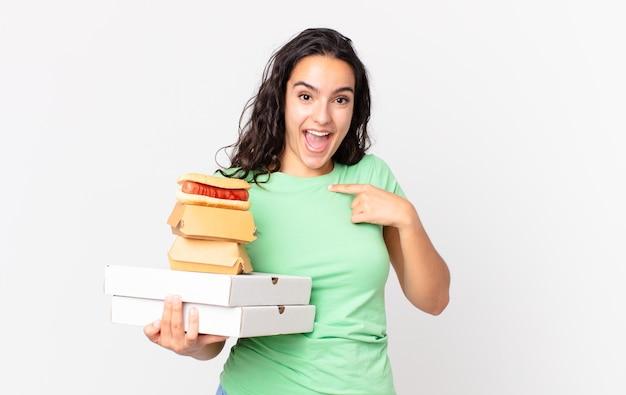 Linda mulher hispânica se sentindo feliz e apontando para si mesma com uma animada e segurando caixas de fast food