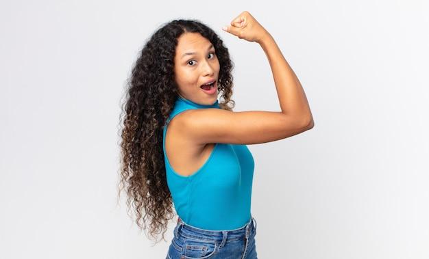Linda mulher hispânica se sentindo feliz, satisfeita e poderosa, flexionando a forma e bíceps musculosos, parecendo forte depois da academia