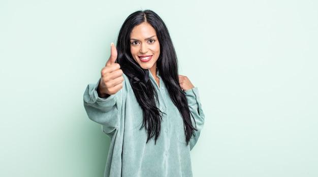 Linda mulher hispânica se sentindo orgulhosa, despreocupada, confiante e feliz, sorrindo positivamente com o polegar para cima