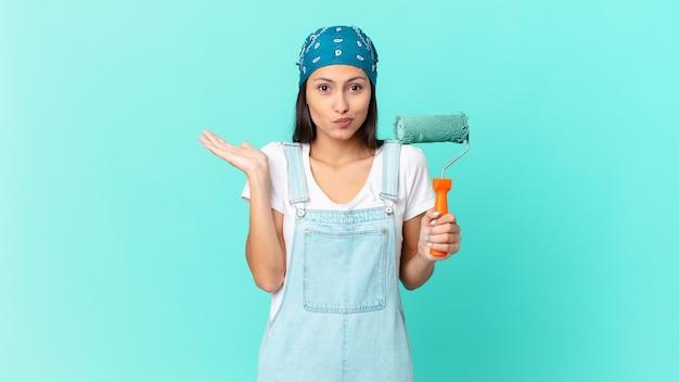 Linda mulher hispânica se sentindo perplexa, confusa e em dúvida. conceito de pintura de casa