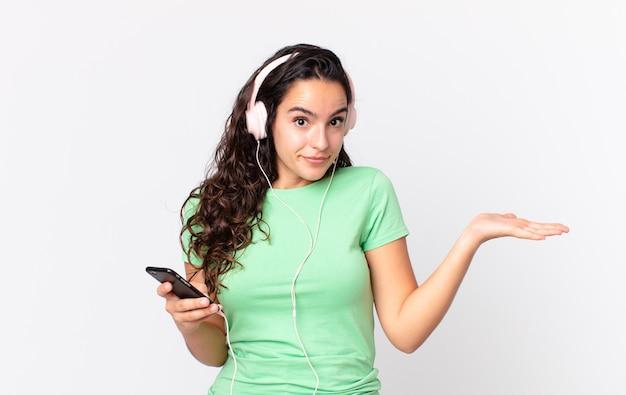 Linda mulher hispânica se sentindo perplexa e confusa e duvidando de fones de ouvido e um smartphone