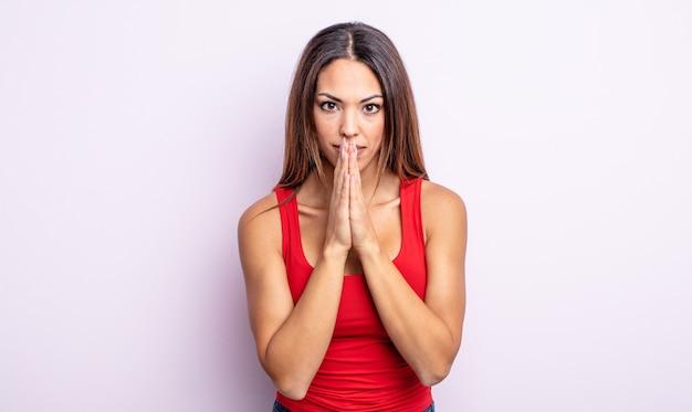 Linda mulher hispânica se sentindo preocupada, esperançosa e religiosa, orando fielmente com as palmas das mãos pressionadas, implorando perdão
