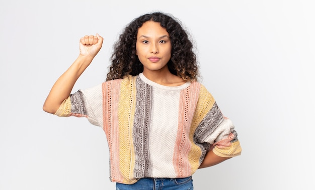Linda mulher hispânica se sentindo séria, forte e rebelde, levantando o punho, protestando ou lutando pela revolução