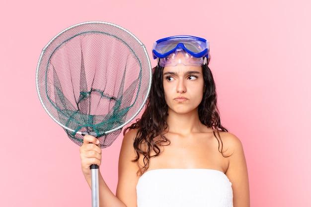 Linda mulher hispânica se sentindo triste, chateada ou com raiva e olhando para o lado com óculos e rede de pesca