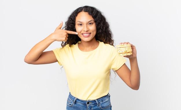 Linda mulher hispânica segurando um bolo de dieta de arroz