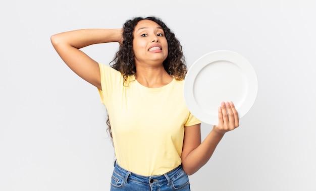 Linda mulher hispânica segurando um prato vazio e limpo