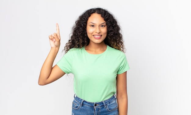 Linda mulher hispânica sorrindo alegre e feliz, apontando para cima com uma das mãos para copiar o espaço