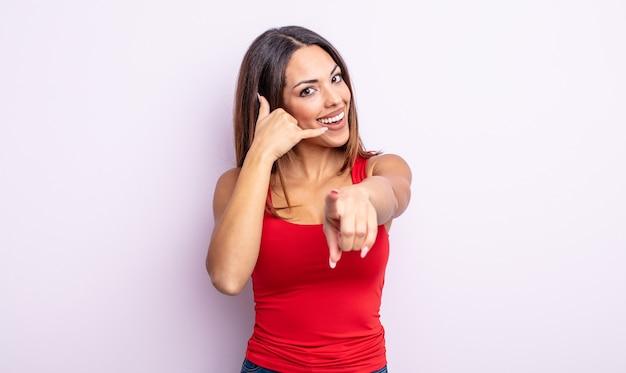 Linda mulher hispânica sorrindo alegremente e apontando para a câmera enquanto faz um gesto depois de ligar para você, falando ao telefone