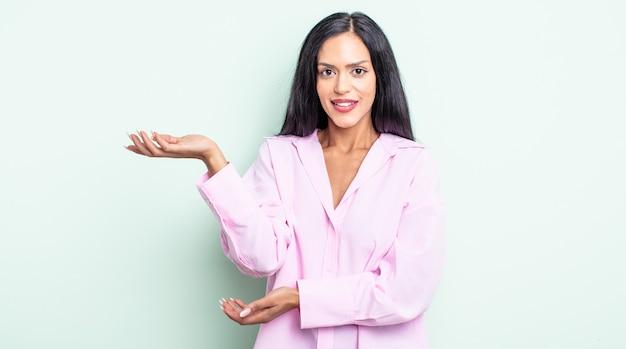 Linda mulher hispânica sorrindo com orgulho e confiança, sentindo-se feliz e satisfeita e mostrando um conceito no espaço da cópia