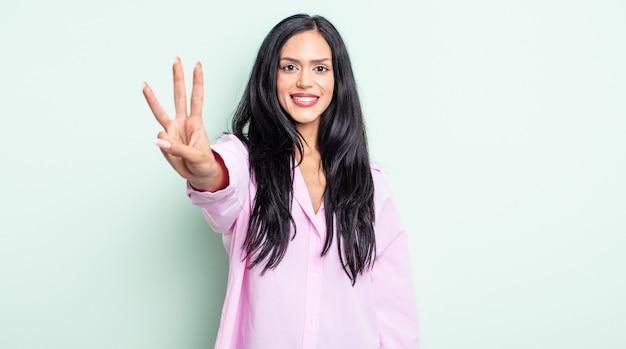 Linda mulher hispânica sorrindo e parecendo amigável, mostrando o número três ou o terceiro com a mão para a frente, em contagem regressiva