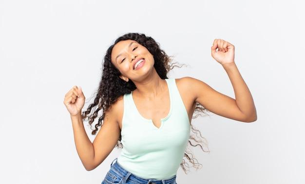 Linda mulher hispânica sorrindo, se sentindo despreocupada, relaxada e feliz, dançando e ouvindo música, se divertindo em uma festa