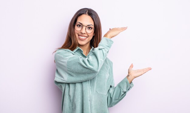 Linda mulher hispânica sorrindo, sentindo-se feliz, positiva e satisfeita, segurando ou mostrando um objeto ou conceito no espaço da cópia