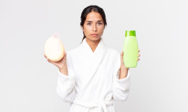 Linda mulher hispânica usando roupão de banho e segurando um shampoo e uma esponja