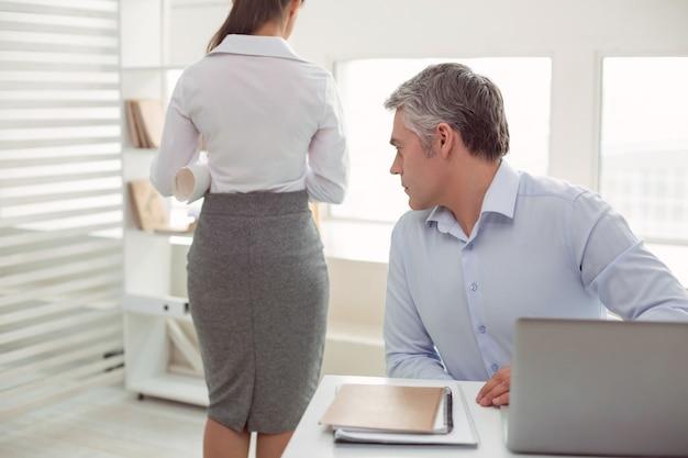 Linda mulher. homem adulto simpático sério sentado à mesa e olhando para sua colega enquanto tem um interesse sexual por ela