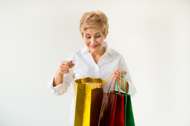 Linda mulher idosa com corte de cabelo curto em uma camisa branca com pacotes em um fundo branco