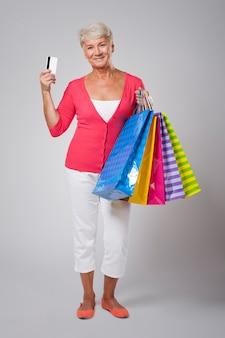 Linda mulher idosa com sacolas de compras e cartão de crédito