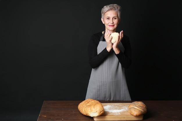 Linda mulher idosa com um avental a preparar pão fresco com massa