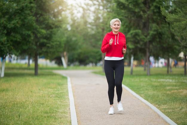 Linda mulher idosa com um corte de cabelo curto corre no parque