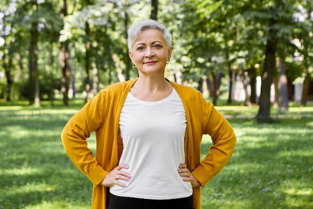 Linda mulher idosa de cabelos grisalhos em casaquinho amarelo e camiseta branca posando no parque verde de verão, mantendo as mãos na cintura, fazendo exercícios físicos, com um sorriso confiante