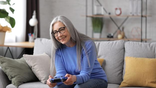 Linda mulher idosa de cabelos grisalhos jogando videogame usando gamepads em casa.