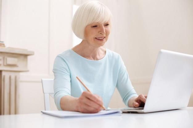 Linda mulher idosa e focada, encontrando dicas úteis online e anotando-as com lápis