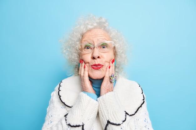 Linda mulher idosa mantém as mãos nas dobras do rosto lábios pintados de vermelho usa óculos o macacão branco tem uma pele bem cuidada