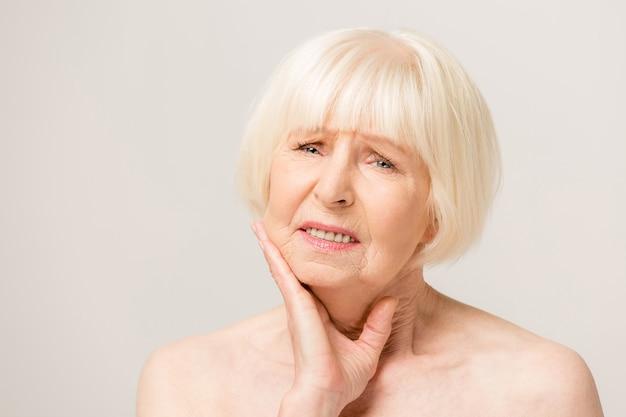 Linda mulher idosa sênior tocando a boca com a mão com expressão dolorosa por causa de dor de dente ou doença dentária nos dentes. conceito de dentista.