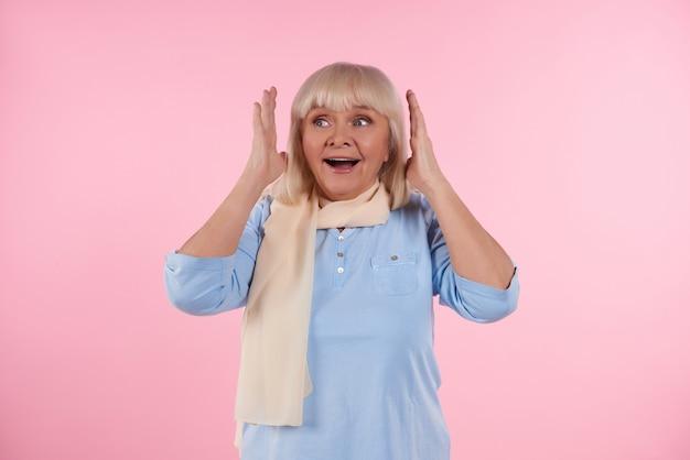 Linda mulher idosa surpreso, isolado no fundo rosa