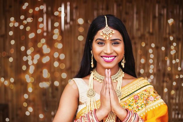 Linda mulher indiana em saree fazendo namaste