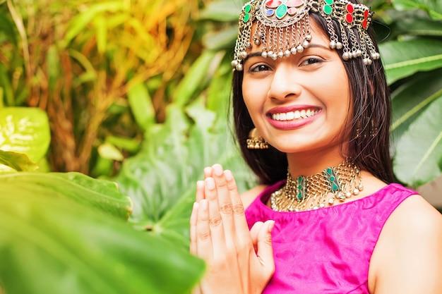 Linda mulher indiana em um vestido tradicional cumprimentando com namaste