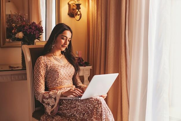 Linda mulher indiana sentada em um quarto de hotel com laptop