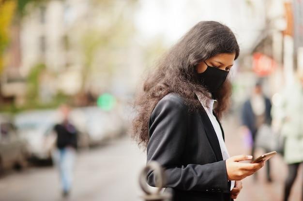 Linda mulher indiana usa máscara facial formal e preta, posando na rua durante a pandemia cobiçosa, assistindo às notícias em seu smartphone.