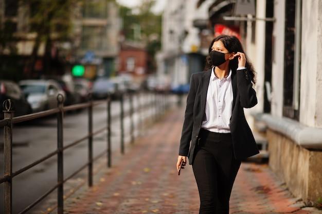 Linda mulher indiana usa máscara facial formal e preta, posando na rua durante uma pandemia cobiçosa, com o celular em mãos.