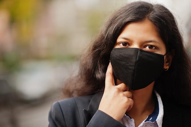 Linda mulher indiana usa máscara facial formal e preta, posando na rua durante uma pandemia cobiçosa.
