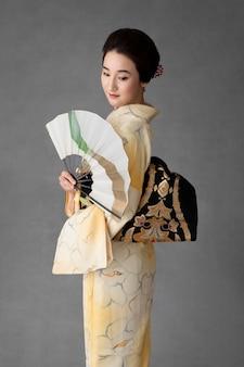Linda mulher japonesa com um leque minimalista