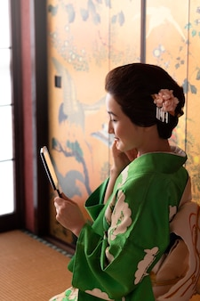 Linda mulher japonesa se olhando no espelho