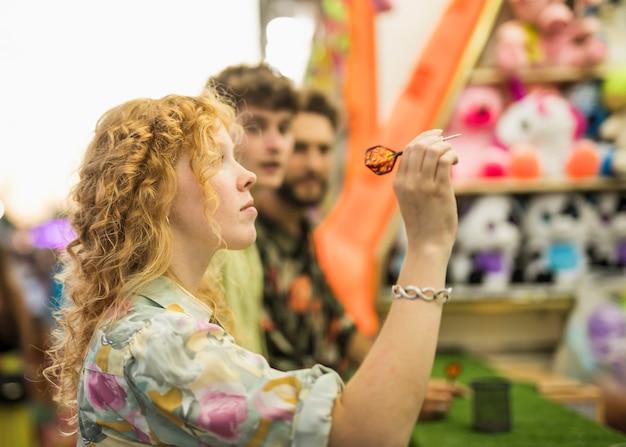 Linda mulher jogando dardos com os amigos