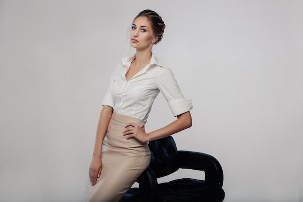 Linda mulher jovem elegante bussines permanente no estúdio com fundo cinza