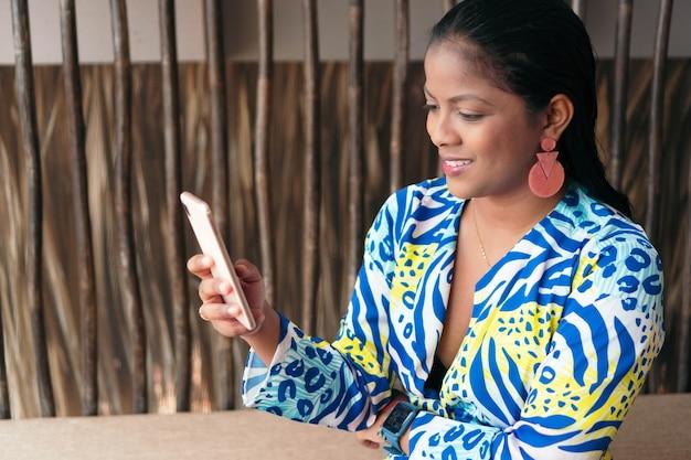Linda mulher latina aproveitando o dia de sol em casa e usando o celular.