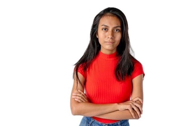 Linda mulher latina com os braços cruzados e uma camisa vermelha, olhando para a frente com uma expressão séria no fundo branco puro.