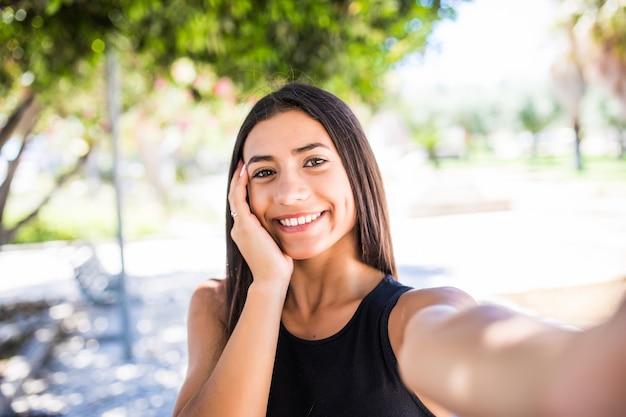 Linda mulher latina com sorriso encantador, olhando para a câmera em pé na rua