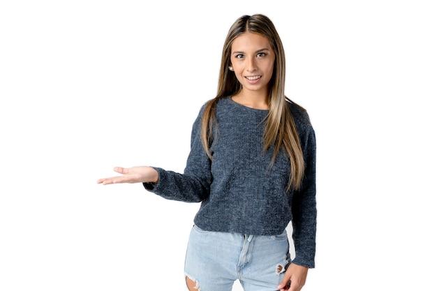Linda mulher latina olhando para a frente com o braço direito estendido e a mão aberta em um fundo branco puro.
